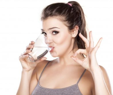 beautiful woman drinks water from a glass and shows delicious